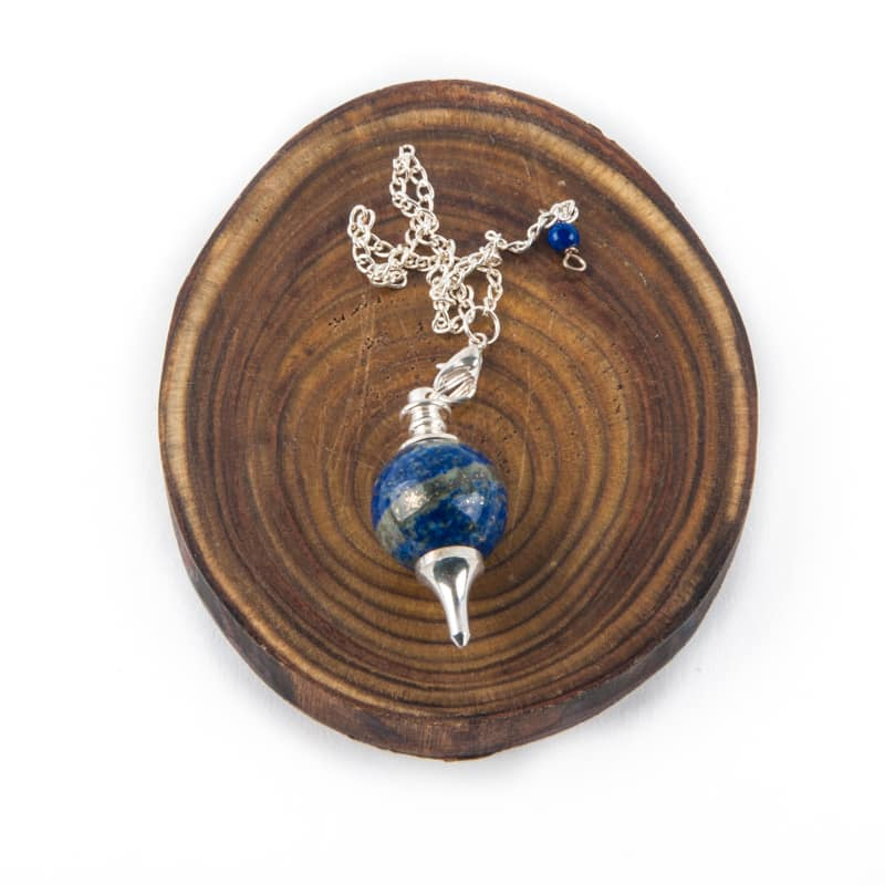 Blauwe pendel zilveren ketting op hout