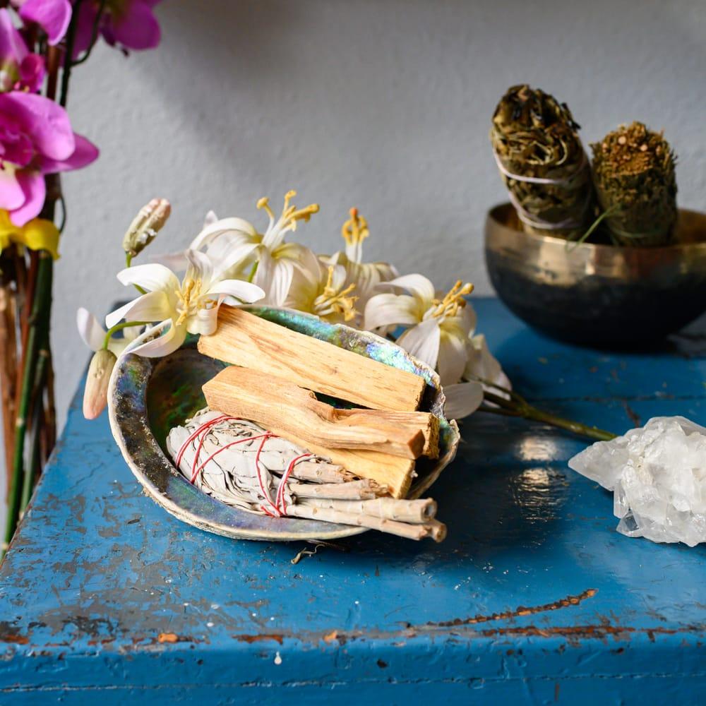 abalone schelp met daarin palo santo en smudge stick bloemen