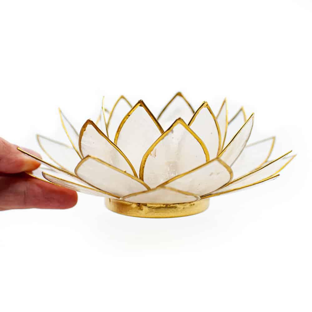 hand houdt witte lotus kaarshouder vast