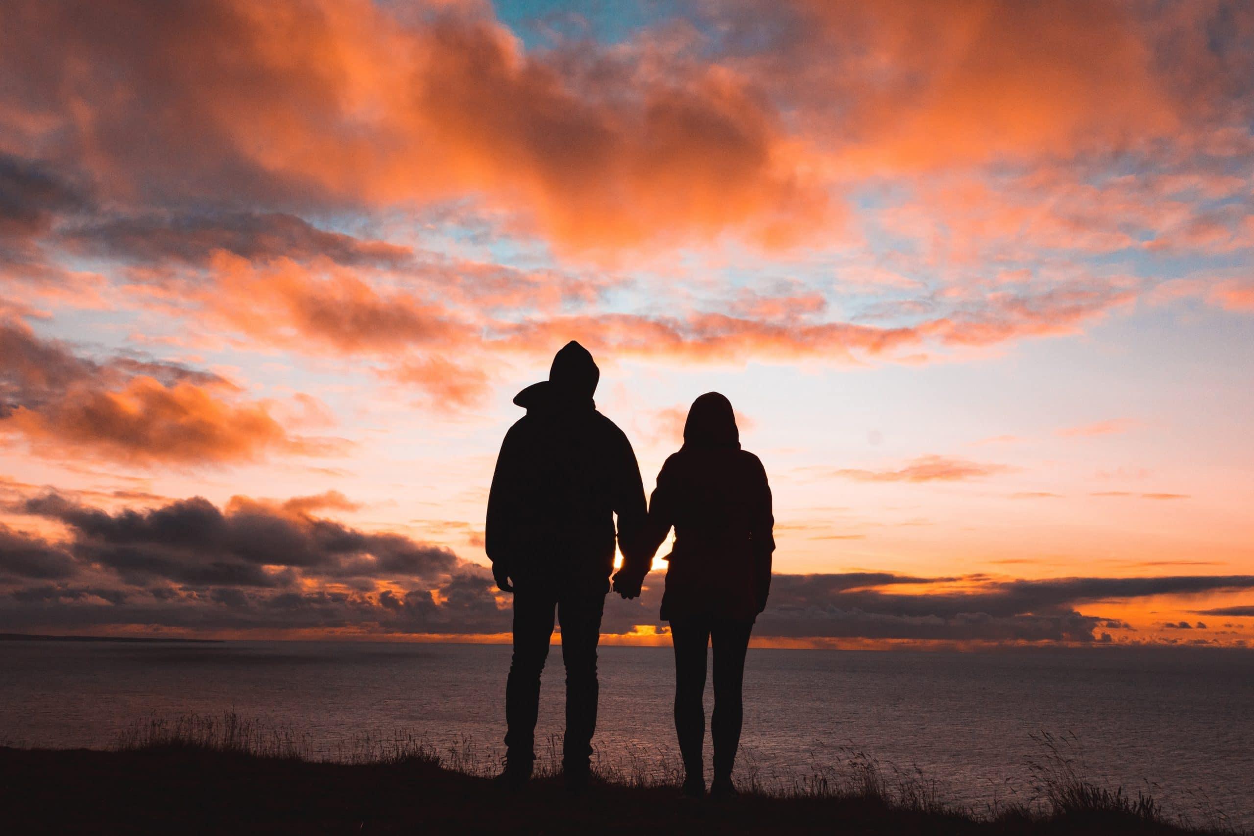 stel hand in hand kijkend naar zonsondergang koppel natuur oranje lucht
