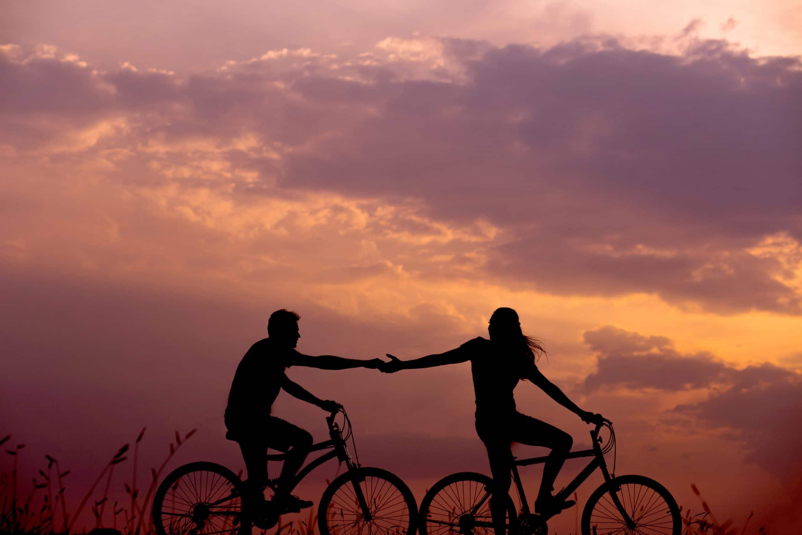 oranje roze lucht en fietsend koppel stel hand in hand