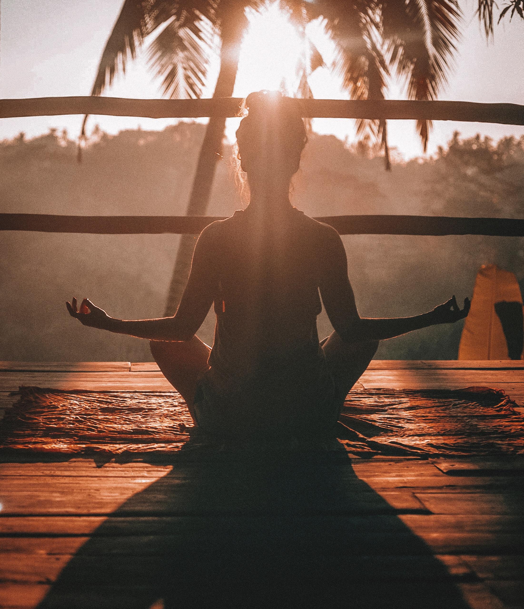vrouw in meditatiehouding in de zon yoga palmboom meditatie