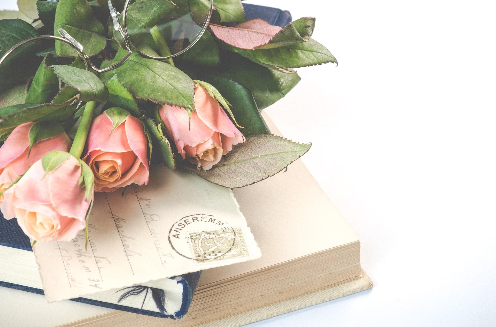 roze rozen bril bovenop kaartje en boeken
