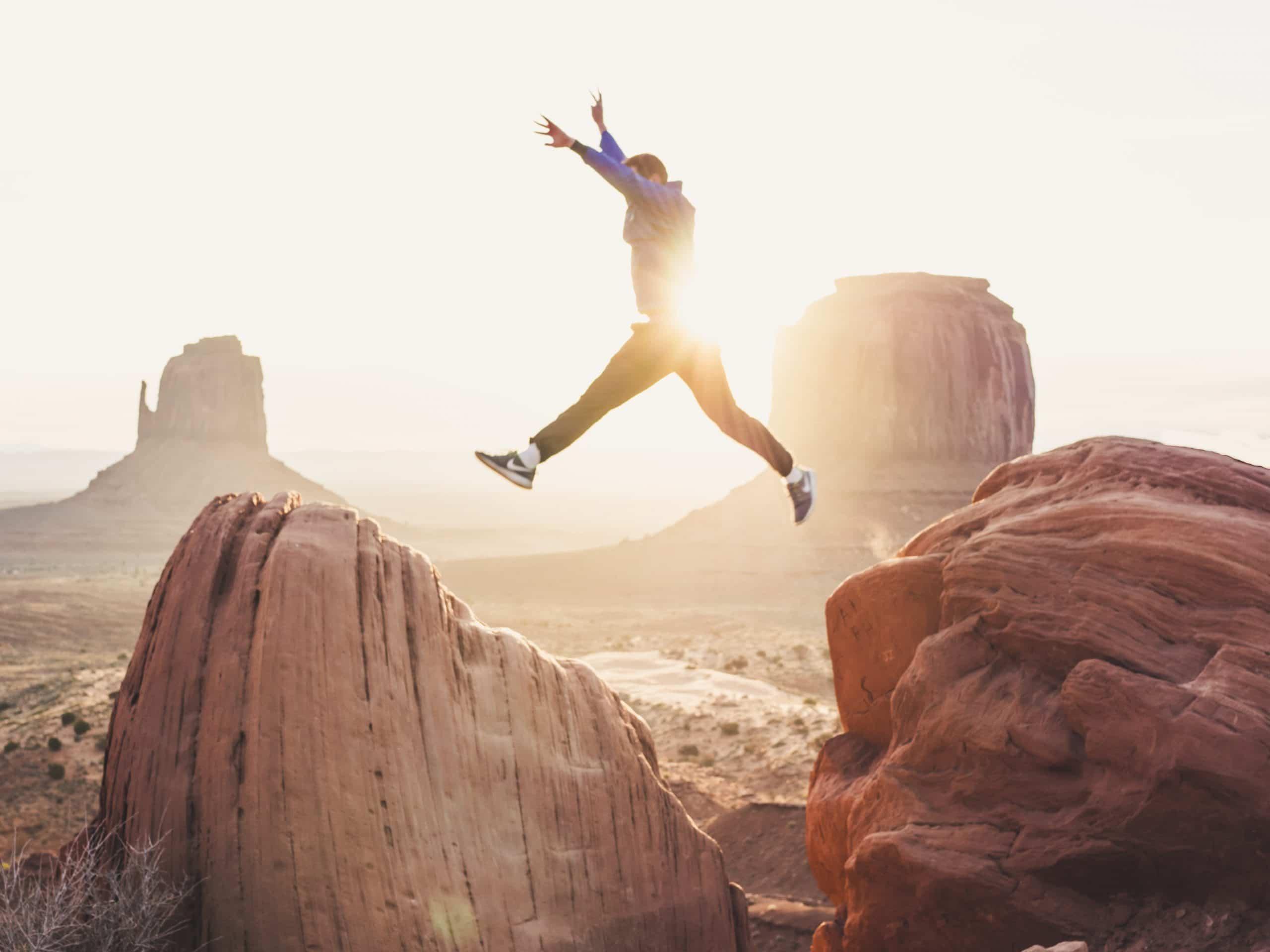 Jongen springt bij zonsondergang